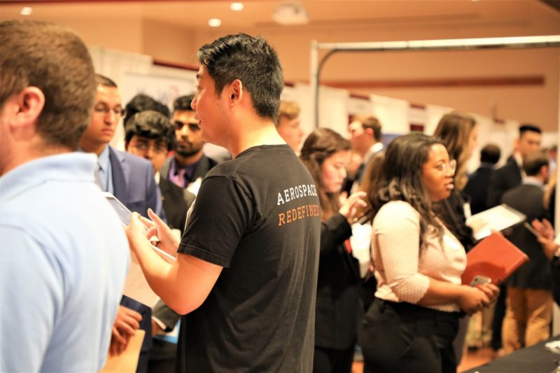 students talk to reps at a career fair